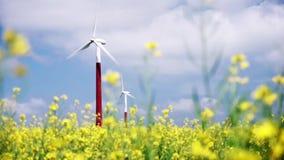 Windturbine op geel raapzaadgebied tegen een blauwe hemel stock footage