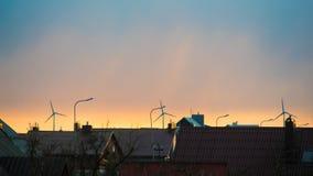 Windturbines achter daken Stock Foto