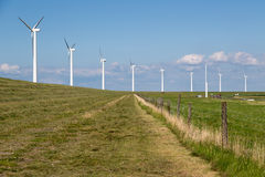 Windturbines along a dike in the Netherlands near a motorway Royalty Free Stock Photography