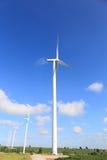 Windturbines die elektriciteit met blauwe hemel produceren Stock Afbeelding