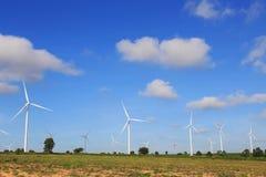 Windturbines die elektriciteit met blauwe hemel produceren Stock Foto's