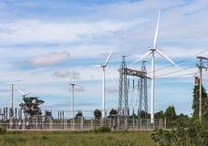 Windturbines die elektriciteit met pylon hulpkantoor van de hoogspannings elektromacht produceren stock foto's