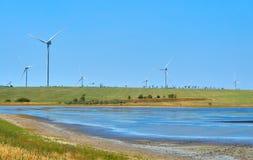 Windturbines die elektriciteit op blauwe hemelachtergrond produceren - Th stock afbeeldingen