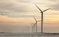 Windturbines at dusk. Evening image of a misty field with windturbines during the winter Stock Photos