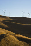 Windturbines on the hills. Windfarm turbines on yellow grassed hills with blue cloudless skys Royalty Free Stock Photo