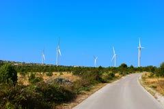 Windturbines, landweg en blauwe hemel Stock Afbeelding