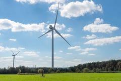 Windturbines op een landelijk landbouwbedrijfgebied stock afbeelding