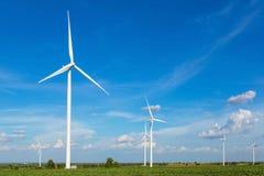 Windturbines op het gebied tegen blauwe hemel die elektriciteit produceren Stock Afbeeldingen