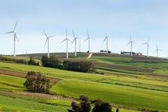 Windturbines op heuvelige uitgestrektheid Stock Foto