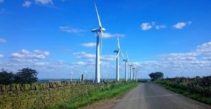 Windturbines tegen een Traditionele Steenmuur stock afbeeldingen