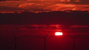 Windturbines tegen rode zonsondergang stock videobeelden