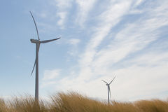 Windturbines. Two windturbines against a blue sky towering over the grass covered dunes Royalty Free Stock Images