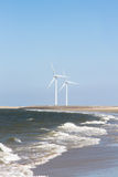 Windturbines. Two wind turbines on the horizon of a beach where the waves of the sea roll on Royalty Free Stock Photography