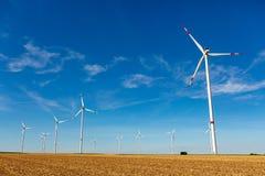 Windturbines in un paesaggio giallo del terreno coltivabile Immagine Stock