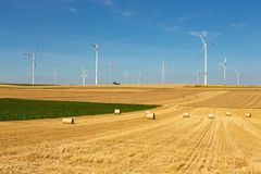 Windturbines in a yellow and green farmland landscape. Beautiful yellow farmland landscape with hay bales and white wind turbines with red stripes generating royalty free stock image