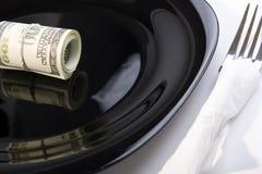 Windungen der Dollar auf einer Platte Stockbilder