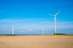 Windwheels behind a barren field Royalty Free Stock Images
