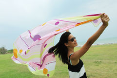 Windy. A girl with a colorful shawl standing by the windy sea Stock Photos