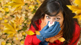 Windy autumn cold and flu. Sick sad woman with flu or cold crying and blowing her nose with a tissue in autumn windy day with leaves flying around. Autumnal Royalty Free Stock Photos