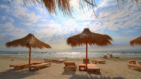 Windy beach. Sunshades and lounges on a windy beach Stock Photo