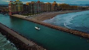 View from above on small yacht during sunset on Mediterranean sea coast near Valencia. Windy and colorful evening in Spain. Filmed on beach without people near stock footage