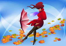 Windy day. Girl in red raincoat with umbrella and turned  foliage behind Royalty Free Stock Image