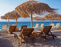 Palapas and lounge chairs on Aigio Beach on the Corinthian Gulf in Greece. A windy day on Aigio Beach on the Corinthian Gulf, located on the Peloponnesian Stock Photography