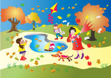 Windy Day in the park. A windy day in the park, with autumn leaves swirling around. A little girl is flying her kite,  a boy is being blown around by the breeze Royalty Free Stock Images