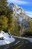 Windy mountain road after the snow was recently plowed away. Mountain road after a snow storm at the mountain top above the storm and just after the snowplow royalty free stock photos