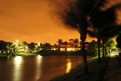 House by lake at night. A house by a lake on a windy night with golden sky background Royalty Free Stock Image