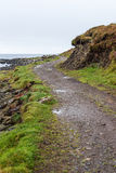Windy path beside the coast. Lonely coastal dirt track near Dunvegan castle in Skye in the highlands of Scotland. The windy path goes through a loch and the Royalty Free Stock Images