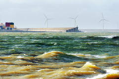 Windy seascape with rough sea. And windmills Stock Photos