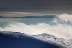 Windy snowfield above clouds and fog at dawn Slovak Carpathians royalty free stock images