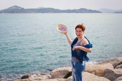 Windy summer days relaxing on coast feeling good. adult woman in glasses and jeans walks on the coast stock photo