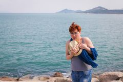 Windy summer days relaxing on coast feeling good. adult woman in glasses and jeans walks on the coast, portrays fright.  royalty free stock image