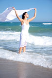 Windy water. Girl relaxing on ocean beach with tissue scarf stock photo