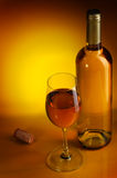Wine. Bottle and glass of wine on a yellow background Royalty Free Stock Photo