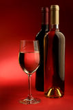 Wine. Bottle and glass of wine on a red background Royalty Free Stock Images