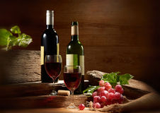 Wine. Still-life with two wine bottles and glass over wooden textured background Royalty Free Stock Images