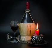 Wine. Bottle decorated with woven bamboo leaves in muted ambience on a black background with two glass cups Royalty Free Stock Images