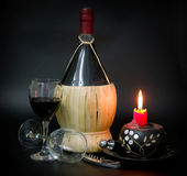 Wine. Bottle decorated with woven bamboo leaves in muted ambience on a black background with two glass cups Stock Photography