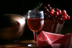 Wine. Leather covered wine bottle, grapes, basket and glass of wine Stock Photo