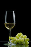Wine. Glass of white wine and grapes on a black background Stock Photo