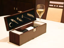 Wine accessories box. White wine in glass with wine accessories in the box stock image