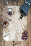 Wine and appetizer set with copy space in center. Glass of red wine, bottle, corkscrewer, blue cheese, grapes, honey Royalty Free Stock Photos