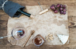 Wine and appetizer set with copy space in center. Glass of red wine, bottle, corkscrewer, blue cheese, grapes, honey Stock Photos