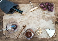 Wine and appetizer set with copy space in center. Glass of red wine, bottle, corkscrewer, blue cheese, grapes, honey Stock Photography