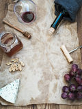 Wine and appetizer set with copy space in center. Glass of red wine, bottle, corkscrewer, blue cheese, grapes, honey Royalty Free Stock Images