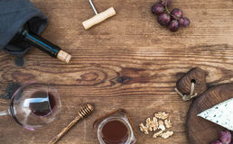 Wine and appetizer set with copy space in center. Glass of red wine, bottle, corkscrewer, blue cheese on serving board Stock Images