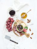 Wine appetizer set. Glass of red, grapes, parmesan. Wine appetizer set. Glass of red wine, grapes, honey, parmesan cheese, meat variety, bread slices, pecan nuts royalty free stock images